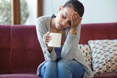Aufnahme einer depressiven jungen Frau mit Kopfschmerzen beim Kaffeetrinken auf dem Sofa zu Hause. Standard-Bild