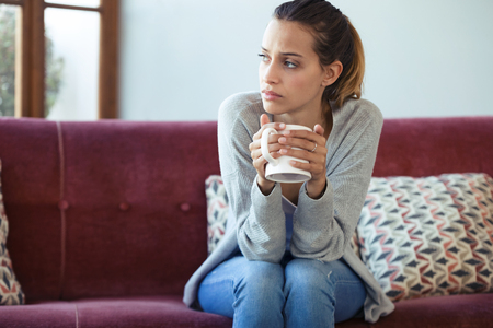 Shot of depressed young woman thinking about her problems while drinking coffee on sofa at home. Banque d'images - 121694218