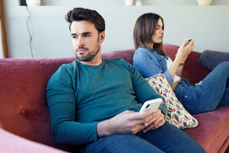 Shot of angry young couple ignoring each other using phone after an argument while sitting on sofa at home.