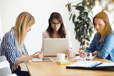 Photo de jolies jeunes femmes d'affaires travaillant sur de nouvelles idées dans un espace de co-working. Banque d'images