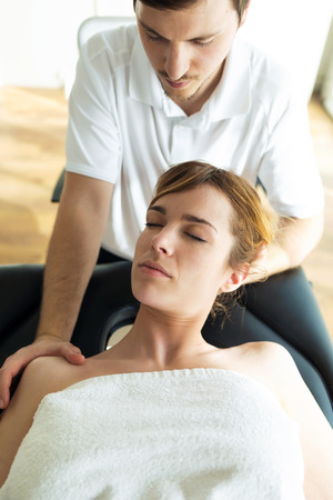 Shot of young physiotherapist doing a neck treatment to the patient in a physiotherapy room. Rehabilitation, medical massage and manual therapy concept. Standard-Bild