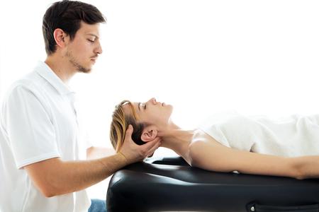 Aufnahme eines jungen Physiotherapeuten, der dem Patienten in einem Physiotherapieraum eine Nackenbehandlung durchführt. Konzept für Rehabilitation, medizinische Massage und manuelle Therapie. Standard-Bild