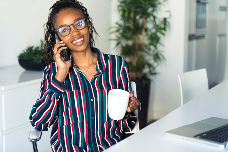 Shot of business young woman talking on mobile phone while drinking coffee in the office.