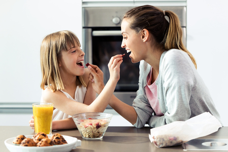 Shot of beautiful mother and daughter feeding cereals to each other at home.