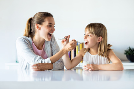 Shot of beautiful mother and daughter feeding yogurt to each other at home. Banco de Imagens