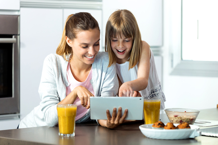 Shot of pretty young mother and her daughter using digital tablet while having breakfast at home. Banco de Imagens