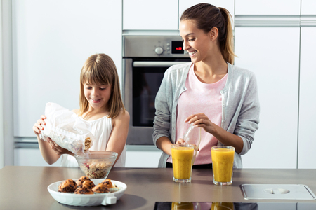 Shot of pretty young mother and her daughter preparing breakfast in the kitchen at home.