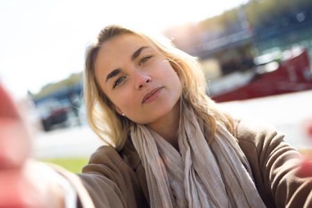 Aufnahme einer schönen jungen Frau, die Selfie mit Smartphone in der Stadtstraße macht. Standard-Bild