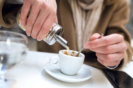 Close-up of a womans hand pouring sugar into the cup of coffee.