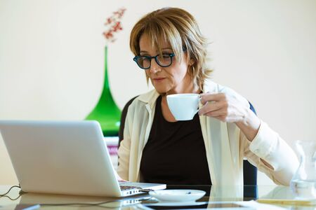 Shot of cheerful confident business woman drinking coffee while working with her laptop in the office.
