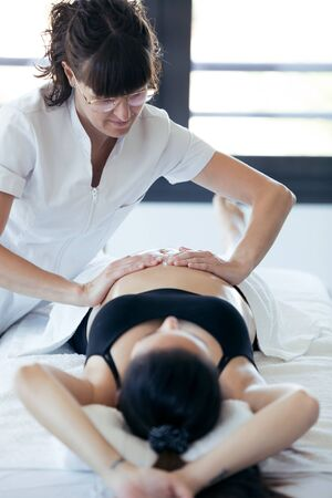 Shot of female physiotherapist massaging tummy on pregnant woman in spa center. 版權商用圖片