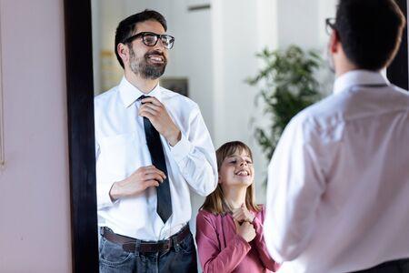 Foto de padre joven guapo arreglando su corbata frente al espejo y su hermosa hija copiándola en casa. Foto de archivo