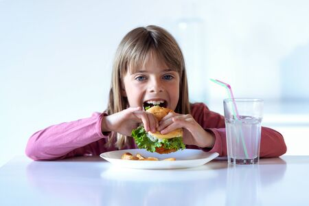 Shot of pretty little girl eating a complete hamburger while looking at camera at home. Stockfoto