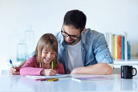 Shot of handsome young father with his daughter drawing on notebook at home.