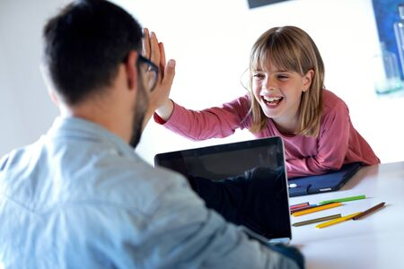 Shot of handsome young father and his pretty daughter giving high five while he working on laptop at home.