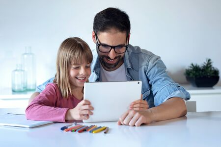 Shot of handsome young father with his little daughter using digital tablet at home.