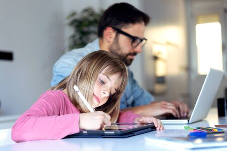 Shot of pretty little girl drawing on her digital tablet while her father working with laptop at home. Stockfoto