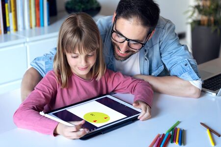 Shot of handsome young father with his daughter drawing with digital tablet at home.