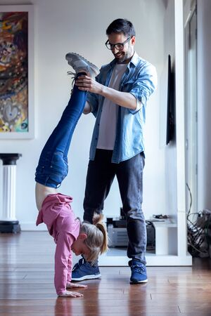 Shot of handsome young father helping to pretty daughter to doing cartwheel at home.