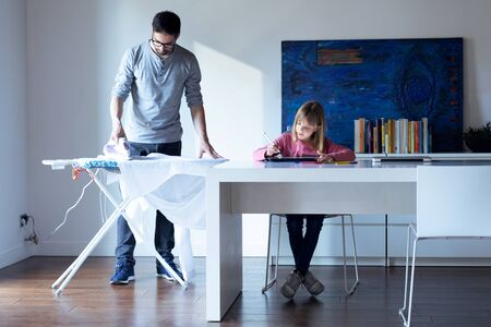 Shot of pretty little girl drawing on notebook while her father ironing a shirt at home. Stockfoto