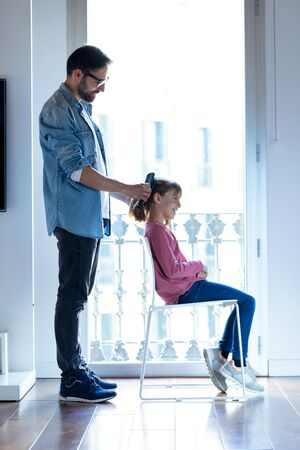 Shot of handsome young father making a ponytail to his daughter while she sitting on a chair at home.