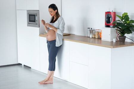 Shot of beautiful pregnant young woman eating yogurt while standing in the kitchen at home.
