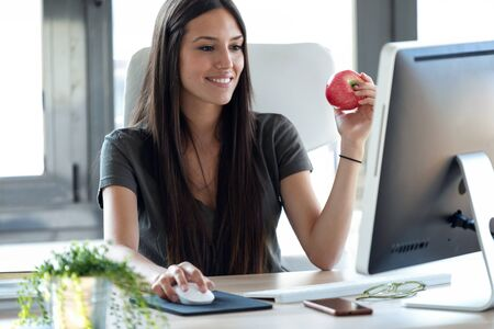 Shot of smiling young business woman eating a red apple while working with computer in the office. Stockfoto