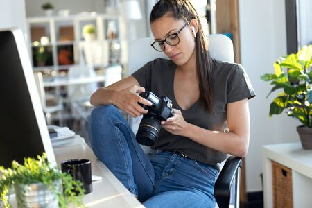 Shot of professional young photographer reviewing the photos she has taken with the camera while sitting in the studio.