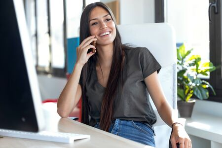 Shot of smiling young business woman talking on mobile phone while sitting in the office. Stockfoto