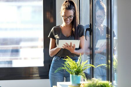Shot of smiling young business woman using her digital tablet while standing next to the window in the office.