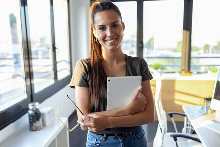 Portrait of smiling young business woman looking at camera while holding digital tablet and standing in the office. Stockfoto