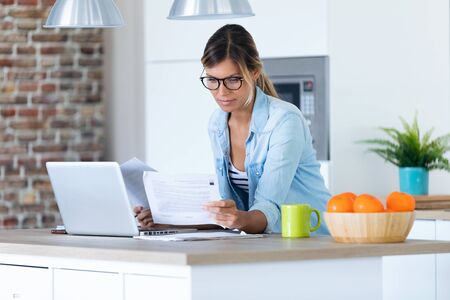 Shot of pretty young woman working with laptop and documents in the kitchen at home. Stockfoto