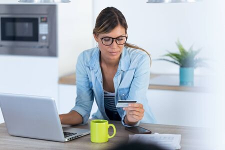 Shot of pretty young woman using her laptpo for shopping online and paying with credit card while sitting in the kitchen at home.