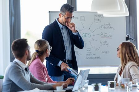 Shot of handsome businessman clearing his throat while explaining a project to his colleagues on coworking place. Stockfoto