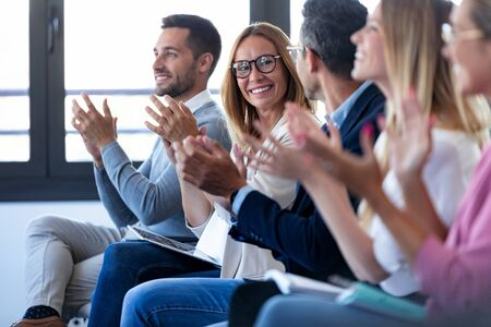 Shot of happy business team clapping after listening the conference while sitting on coworking space.