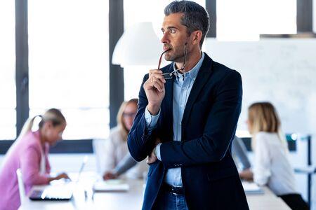 Foto de guapo empresario mirando hacia los lados mientras sus colegas están trabajando en el lugar de coworking.