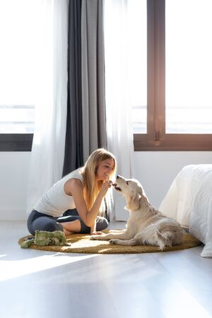 Shot of pretty young woman feeding her dog while having fun at home. Stockfoto