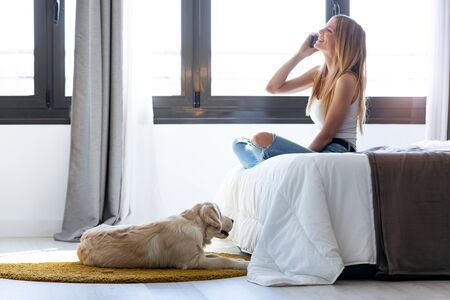 Shot of pretty young woman talking on mobile phone while staying with her dog at home.