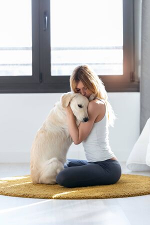 Shot of pretty young woman hugging her dog while sitting on the floor at home. Stockfoto