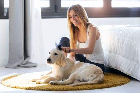 Shot of pretty young woman brushing her dogs hair while sitting on the floor at home.