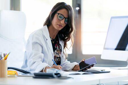 Ujęcie całkiem młoda kobieta ginekolog pracuje z jej telefonem komórkowym przed rozpoczęciem konsultacji w klinice. Zdjęcie Seryjne