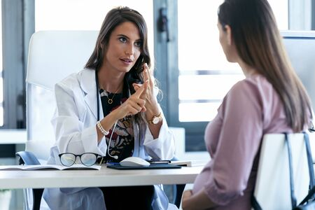 Shot of serious young gynecologist giving guidelines to his pregnant patient in the clinic. Stockfoto