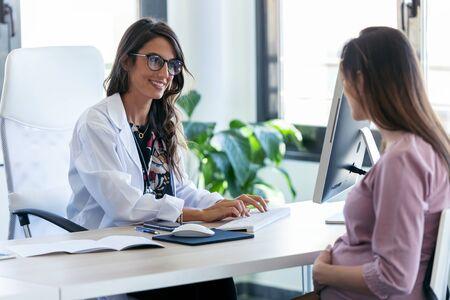 Foto de ginecólogo bastante joven revisando el historial médico de su paciente embarazada con computadora en la clínica.