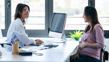 Shot of pretty young woman gynecologist reviewing the medical history of her pregnant patient with computer in the clinic. Stockfoto