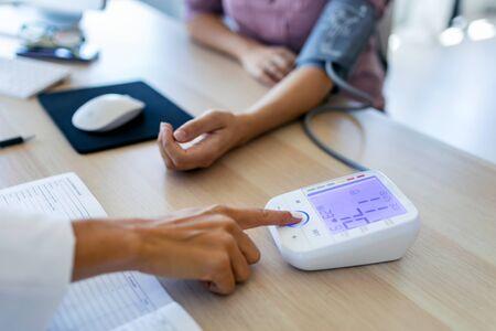 Nahaufnahme der Frauenärztin, die den Blutdruck ihrer schwangeren Patientin in der Klinik überprüft. Standard-Bild