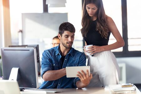 Shot of concentrated young woman standing next to her man colleague pointing at something on digital tablet while working together in office. Stock Photo