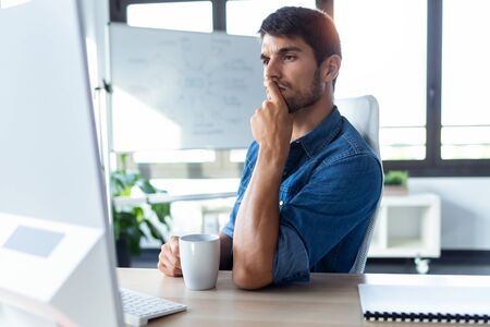 Shot of software developer thinking in new project while working with computer in the modern startup office.