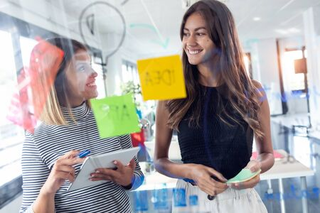 Shot of two business young women working together on wall glass with post it stickers in the modern startup office.