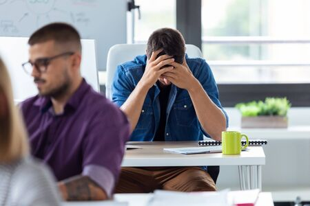 Shot of young businessman holding his face with hands while sitting at the desk in the creative office. Stressful day at the office.