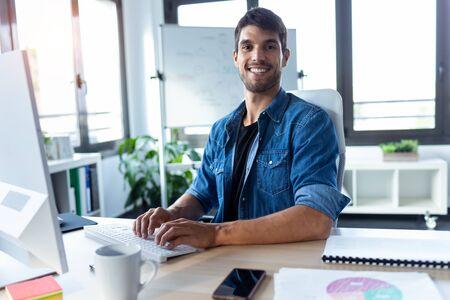 Foto de desarrollador de software mirando a la cámara mientras trabaja con la computadora en la oficina de inicio moderna.